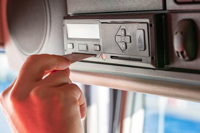 Chauffeur de camion insérant carte conducteur dans tachygraphe pour gestion donnees legales SDEI